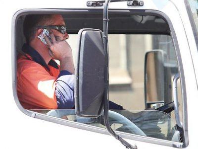 Amendă și suspendarea permisului pe 3 luni pentru un șofer de camion surprins cu telefonul la volan